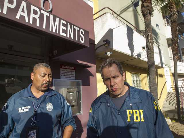 Law enforcement agents enter the apartment building where LAPD and an FBI task force arrested 26-year-old Ammar Harris. (AP)