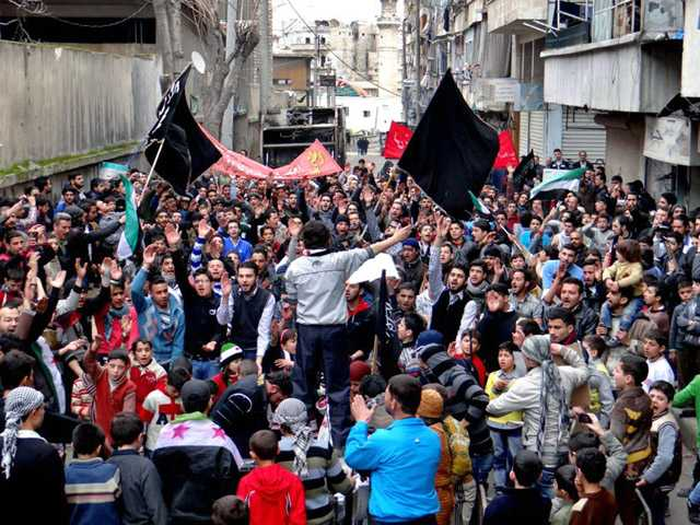 Anti-Syrian regime protesters holding banners and chanting slogans, during a demonstration in the neighborhood of Bustan Al-Qasr in Aleppo, Syria.