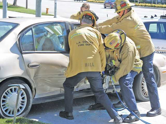 "Firefighters from Fire Station No. 126 use the ""jaws of life"" to gain access to a woman on the passenger side of a Chevrolet sedan that collided with a Toyota Avalon at the corner of McBean Parkway and Town Center Drive in Valencia on Friday."