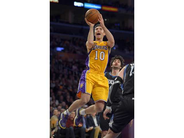 Los Angeles Lakers guard Steve Nash, left, puts up a shot as Minnesota Timberwolves guard J.J. Barea on Thursday in Los Angeles.