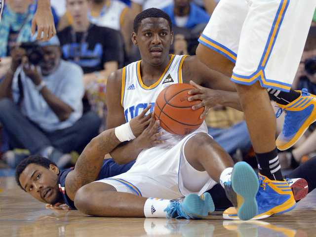 Arizona guard Jordin Mayes, left, and UCLA guard Jordan Adams vie for a loose ball during the first half on Saturday, in Los Angeles.