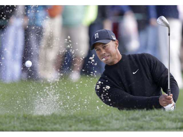 Tiger Woods hits out of a bunker on the fourth hole during the third round of the Honda Classic golf tournament. (AP)