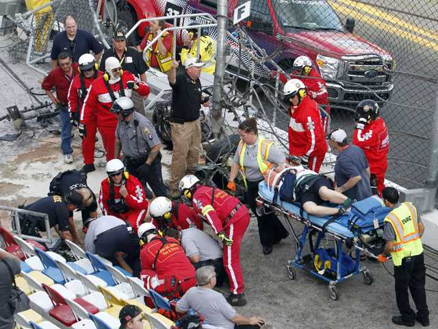 Injured spectators are treated after a crash at the conclusion of the NASCAR Nationwide Series auto race Saturday, Feb. 23. (AP)