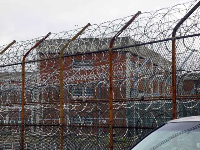 This March 16, 2011 file photo shows a barbed wire fence outside inmate housing on New York's Rikers Island correctional facility in New York.