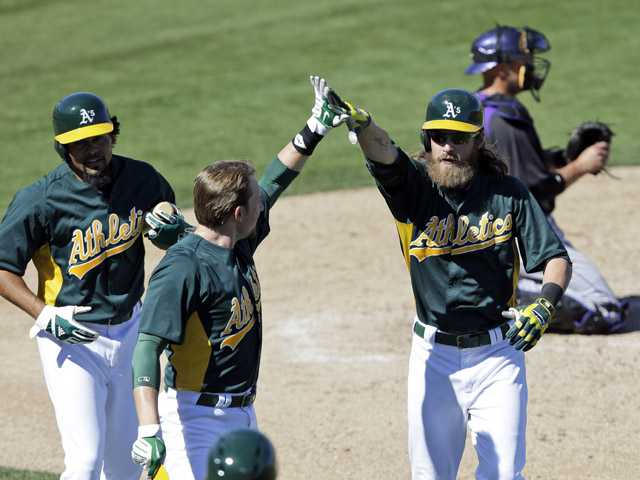 Oakland Athletics' Josh Reddick is met at the plate by teammates Jed Lowrie and Coco Crisp, after driving them in with a three-run home run. (AP)