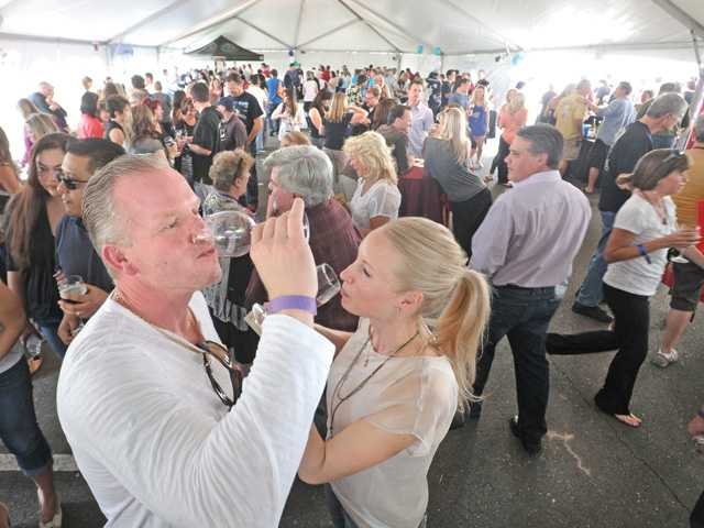 John and Heidi Koonce join hundreds of attendees as they sample a wine at the Third Annual Santa Clarita Wine Fest, which was held in the Bridgeport Marketplace parking lot on Saturday afternoon. (Dan Watson/The Signal )