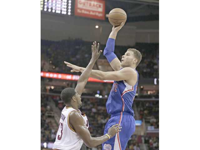 Los Angeles Clipper Blake Griffin, right, shoots over Cleveland Cavalier Tristan Thompson on Friday in Cleveland.