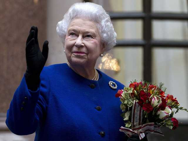 Britain's Queen Elizabeth II looks up and waves to members of staff of The Foreign and Commonwealth Offic. (AP)