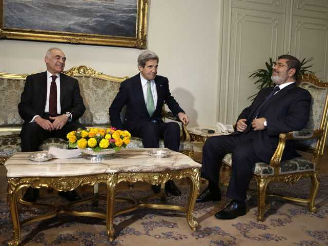 Egyptian Foreign Minister Mohammed Kamel Amr, U.S. Secretary of State John Kerry and Egyptian President Mohamed Morsi take their seats at their meeting at the Presidential Palace in Cairo, Egypt. (AP)