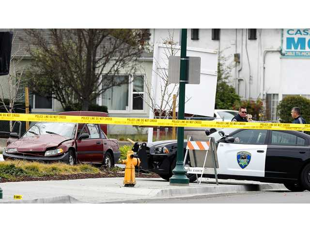 Police investigate the scene of an officer-involved shooting near an intersection, Sunday in Hayward.