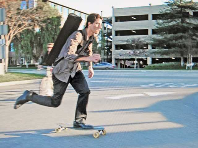 Brazil carries his violin on his back as he rides his skateboard to the Target parking lot on Thursday.