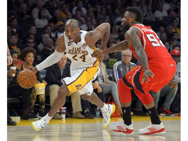 Los Angeles Lakers guard Kobe Bryant, left, drives toward the basket as Atlanta Hawks forward DeShawn Stevenson defends on Sunday in Los Angeles.