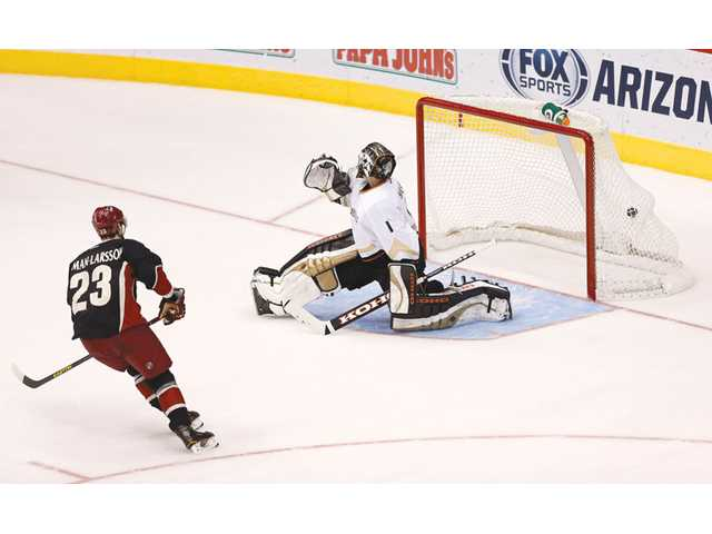 Phoenix Coyote Oliver Ekman-Larrson (23) scores the game-winning goal as Anaheim Ducks goalie Jonas Hiller defends on Monday in Glendale, Ariz.
