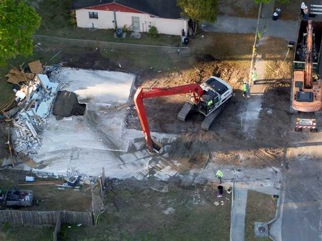 In this aerial photo demolition workers pick up remnants from the home of Jeff Bush who was swallowed when a huge sinkhole opened up under his bedroom.