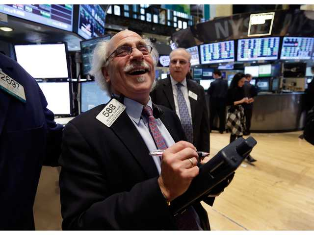 Trader Peter Tuchman smiles as he works on the floor of the New York Stock Exchange Tuesday.