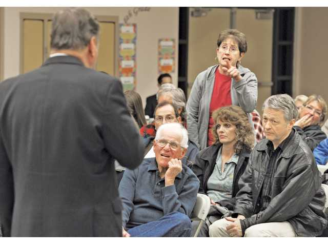 Attendees listen as Ruthann Levinson, standing, of Canyon Country asks a question about a car pool lane near Placerita Canyon of Mayor Bob Kellar at the Mayor's town hall meeting held at Fair Oaks Ranch Community School in Canyon Country.
