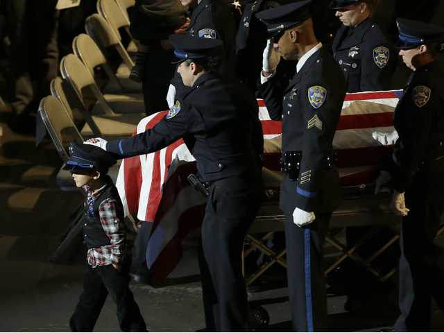Joaquin Wu, 5, leads his mother's casket, containing Santa Cruz Detective Elizabeth Butler, following a memorial service Thursday, at HP Pavilion in San Jose. (AP)