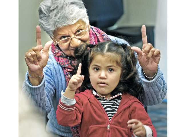 Letty Mendez, and Jamie Grado, 3, of Canyon Country, count along with the group during bilingual story time held at the Jo Anne Darcy Library in Canyon Country on Thursday morning. The program is held free of charge on Thursday mornings from 10-11 a.m. and educates children from 9 months to 4 years in English and Spanish through storytelling and song. (Dan Watson/The Signal)
