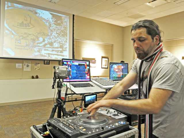 David Cabrera operates a live fideo mixing station to create an on-the-spot visual display during the Art Slam at the Newhall Library on Thursday night. Signal photo by Jonathan Pobre