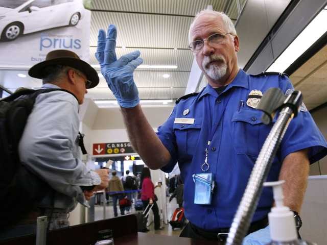 In this Jan. 4, 2010 file photo, TSA officer Robert Howard signals an airline passenger forward at a security check-point at Seattle-Tacoma International Airport in SeaTac, Wash.
