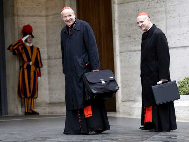 Cardinal Christoph Schoenborn, center, and Cardinal Angelo Comastri arrive for an afternoon meeting, at the Vatican on Friday.
