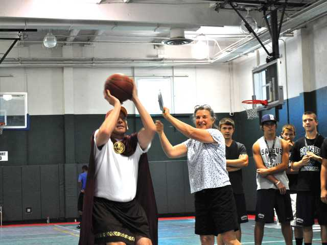 "Special Olympics Coach ""Spike,"" left, shoots free throws during the one-on-one challenge with Special Olympics athlete Lindsay Kautiainen during last year's event."