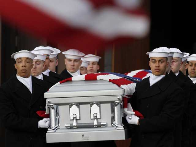 Two Navy Honor Guard teams carry two caskets of remains as they depart Fort Meyer Memorial Chapel during services to honor two sailors from the Civil War ship, the USS Monitor on Friday in Arlington, Va.
