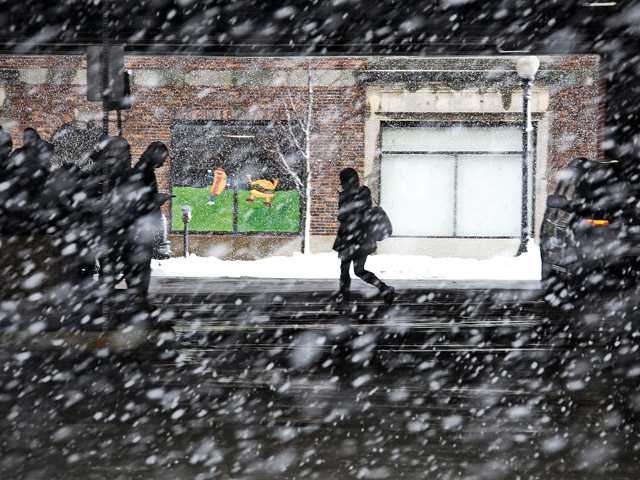 A woman makes her way across the bus station in downtown New Bedford, Mass., as heavy snow falls Friday.