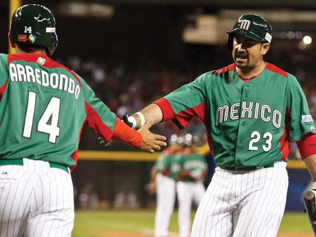 Mexico's Adrian Gonzalez, right, congratulates Eduardo Arredondo (14) after Arredondo scores a run against the United States in a World Baseball Classic baseball game on Friday in Phoenix.
