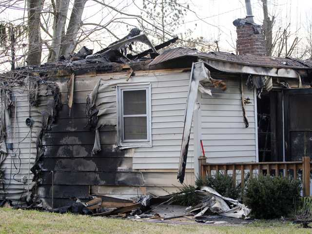 This Sunday photo shows the charred remains of a home after a fire erupted, Saturday in Gray, Ky, killing two adults and five children inside.(AP)