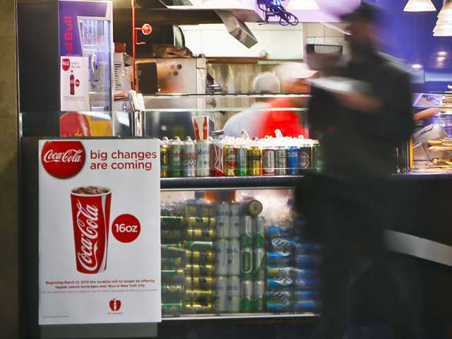 A Coca-Cola poster about the city's new beverage ban is displayed at a pizza shop, Friday, March 8 at New York's Penn Station. (AP)