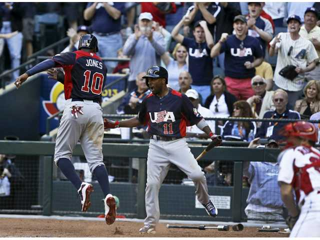 United States hitter Adam Jones (10) celebrates his run scored against Canada with teammate Jimmy Rollins (11) on Sunday in Phoenix.