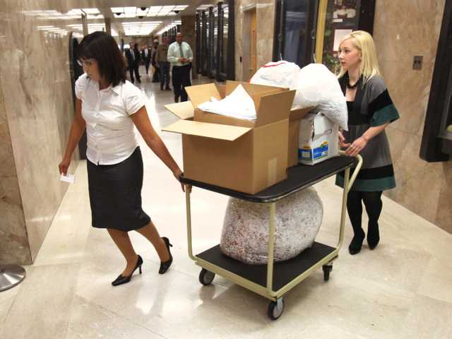 In this April 13, 2010 file photo, CSU Stanislaus students Alicia Lewis, left, and Ashli Briggs, move a cart full of shredded documents they say they found on campus.
