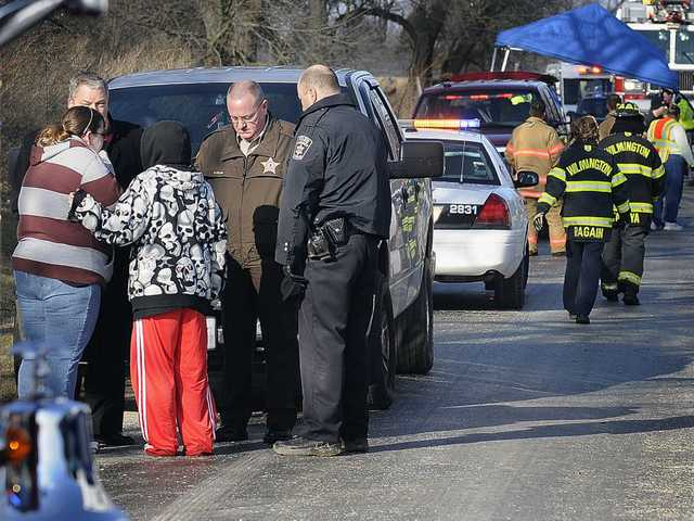 Will County Sheriff's officials and a Wilmington Police officer inform women waiting at the scene near Wilmington, Ill., that the bodies of four teenagers were in a car discovered submerged in Forked Creek on Tuesday morning.
