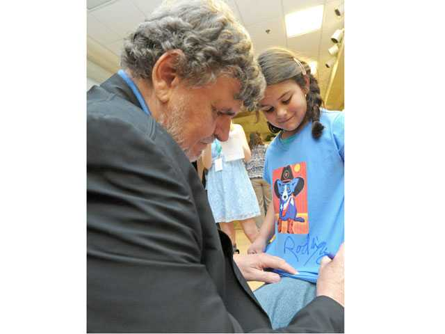 "Artist George Rodrigue, best known for his ""Blue Dog"" series of paintings, signs a T-shirt for first-grader Emily Dominguez at North Park Elementary School on Tuesday. The presentation was Rodrigue's first in California. (Jonathan Pobre/The Signal)"