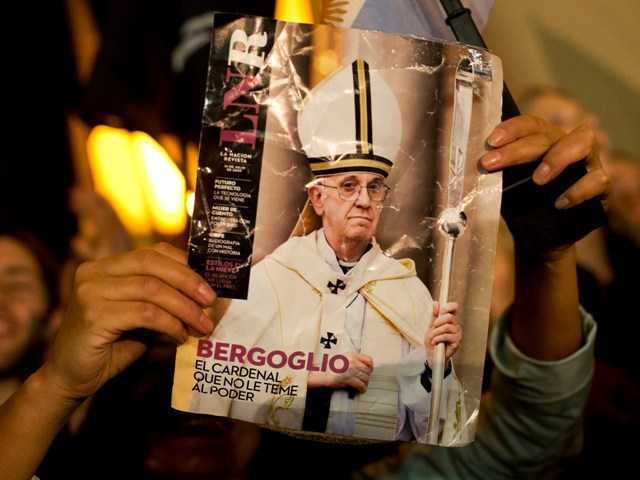 A worshiper holds up the front page of a magazine showing a photograph of Jorge Mario Bergoglio during celebrations in Buenos Aires.