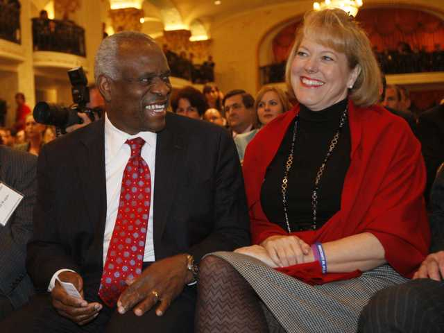 In this Nov. 15, 2007 file photo, Supreme Court Justice Clarence Thomas sits with his wife Virginia Thomas in Washington.