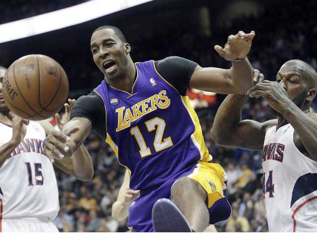 Los Angeles Lakers center Dwight Howard (12) and Atlanta Hawks forward Ivan Johnson (44) battle for a rebound in Atlanta on Wednesday.