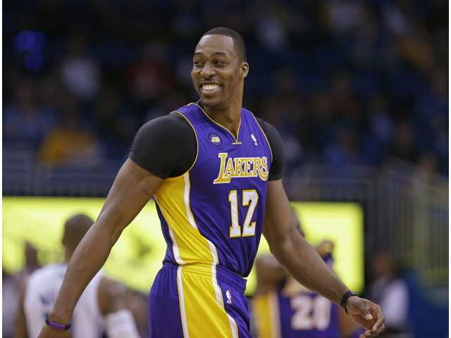 Los Angeles Lakers center Dwight Howard (12) smiles as walks on the court against the Orlando Magic on Tuesday in Orlando, Fla.
