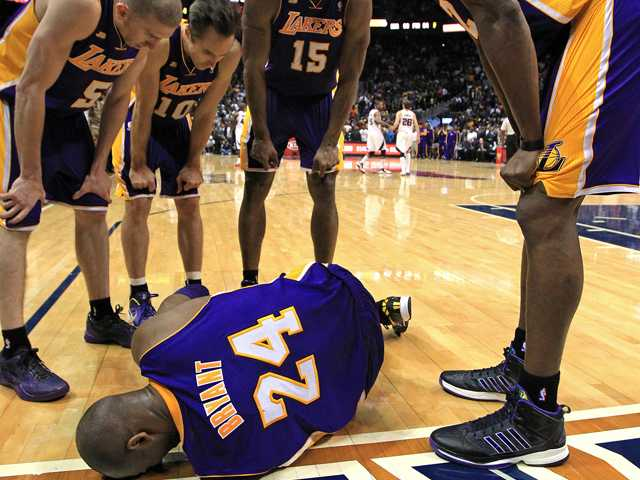 Los Angeles Lakers' Steve Blake, from left, Steve Nash, Metta World Peace and Dwight Howard gather around Kobe Bryant as he lays on the floor after being injured. (AP)