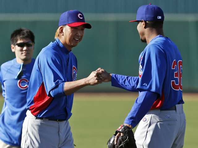Chicago Cubs' Kyuji Fujikawa, center, of Japan, gets a fist bump from teammate Edwin Jackson, right, as interpreter Ryo Shinkawa looks on during a spring training baseball workout in Mesa, Ariz. (AP)