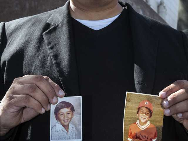 Michael Duran, a plaintiff in a sex abuse settlement with the Roman Catholic Archdiocese of Los Angeles, holds up pictures of himself when he was a child during a news conference. (AP)