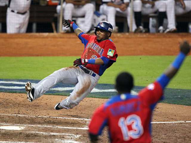 Dominican Republic's Erick Aybar slides safely into home on an RBI single by Jose Reyes against the United States.