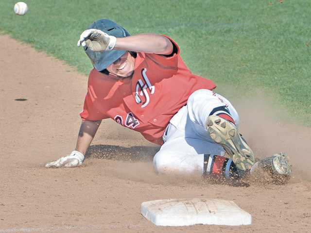 Hart baserunner Joseph Bilbo slides into third base before the throw arrives on Friday at Hart High. The Indians beat Canyon 5-4.