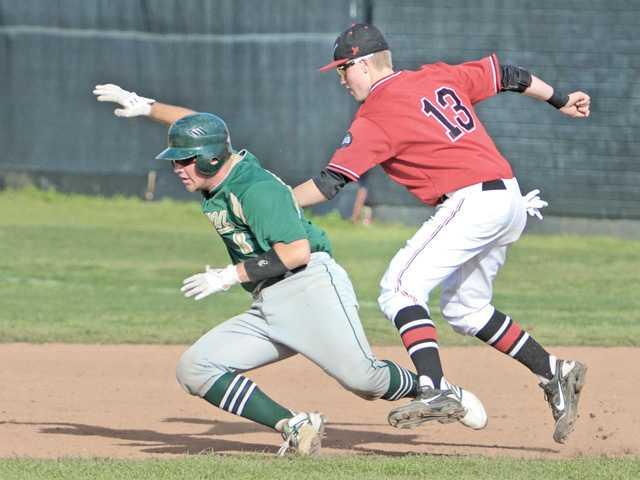 Hart's Austin Russ (13) tags out Canyon's Justin Stark in a rundown Friday at Hart High.