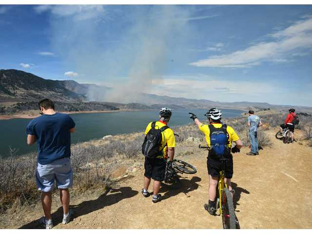Onlookers stop to watch the fire on the east side of Horsetooth Reservior west of Fort Collins, Colo., on Friday.