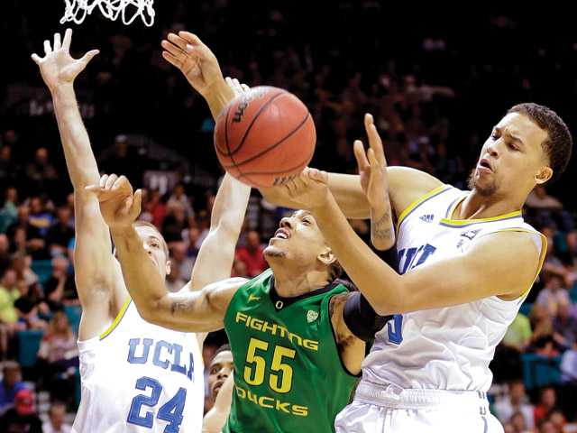 UCLA's Kyle Anderson, right, blocks a shot by Oregon's Tony Woods as Travis Wear (24) helps defend Saturday in Las Vegas.