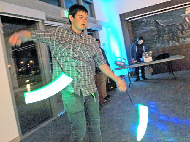 "Jordan Berger of Valencia twists glow sticks as disc jockey Victor Martinez plays dance music during the first ""Art Slam"" display of themed art in downtown Newhall earlier this month. The monthly celebrations of art are part of plans to turn Newhall into an arts and entertainment district. Signal photo by Jonathan Pobre"