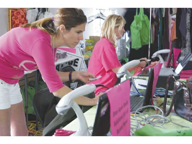 Kal DePaco, left, and Shelly Gomez, founders of Dress On A Dime, take care of sales in Valencia on Sunday.