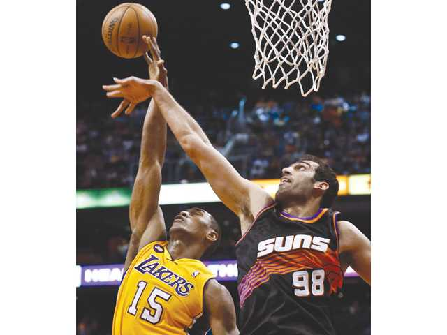 Los Angeles Laker Metta World Peace (15) gets fouled as he goes up for a shot against Phoenix Sun Hamed Haddadi on Monday in Phoenix.